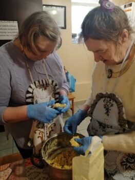 Pacjenci zakładu przygotowujący szarlotkę